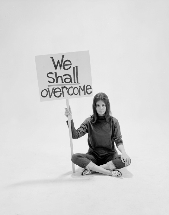"Writer Gloria Steinem sitting cross-legged on floor w. sign ""We Shall Overcome"""